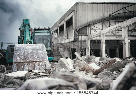 Excavators machine in construction site demolishing existing building for new construction project. Made with shallow depth of field concept focus at shovel