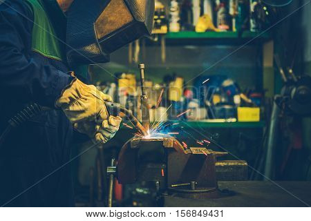Small Garage Welding Works. Welder in Protective Mask Welding Metal Elements. Electric Welding.