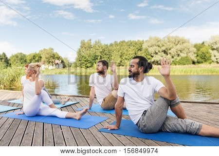 yoga, fitness, sport, and healthy lifestyle concept - group of people sitting in half lord of the fishes pose on mat outdoors on river or lake berth