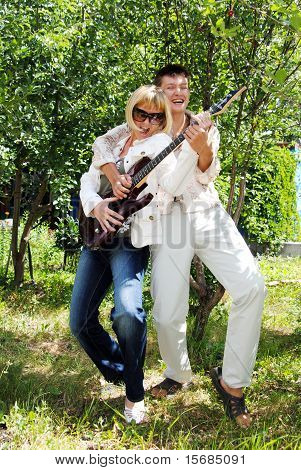 Young Mum And The Son On The Nature In The Summer With An Electroguitar