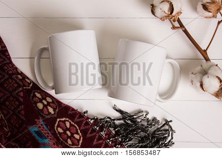 Two white mugs pair of cups Mockup. Cozy atmosphere wooden background cotton and wool decorations for winter gifts.