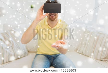 technology, augmented reality, gaming, entertainment and people concept - close up of young man with virtual headset or 3d glasses playing videogame at home over snow