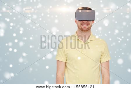 technology, augmented reality, winter, christmas and people concept - happy young man with virtual headset or 3d glasses over gray background and snow