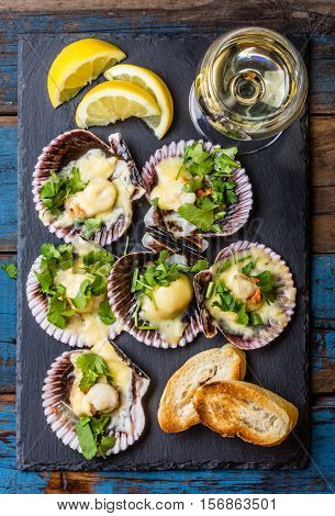Seafood. Shellfish. Baked scallops on slate plate with lemon, cilantro, bread and white wine on wooden blue background. Top view