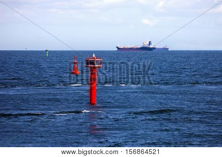 Cargo ship and buoy at open sea.