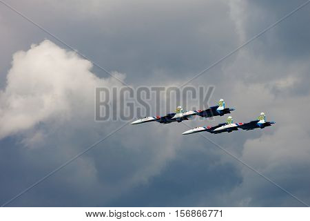Aerobatic Team Russian Knights At Air Show. Cloudy Sky In The Background