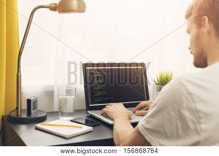 website freelance programmer working from home. sitting by the table