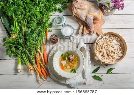 Homemade Chicken Noodle Soup With Ingredients On Wooden Table