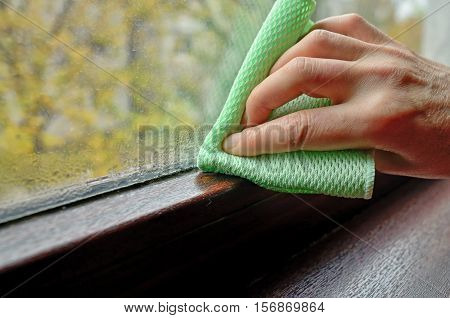 Woman cleaning water condensation on window, close up