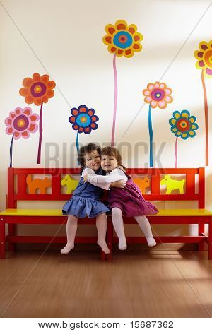 Two Little Girls Smile And Hug At School