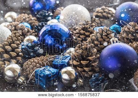 Christmas background with blue ornaments and snowy pinecone. Christmas party decoration with shiny balls.