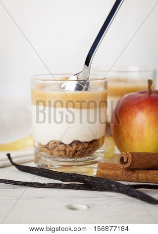 Dessert with cinnamon-flavored applesauce, vanilla-flavored cream and cake crumbles in a glass, arranged with ingredients on table
