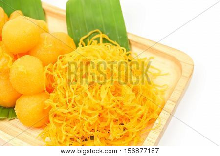 Thai sweet dessert (Med khun Thong Yod Foy Thong) on a wooden plate with green banana leaf isolated on white background Thai traditional desserts