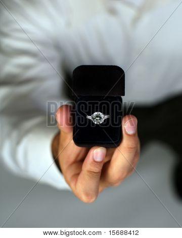 ein Mann vorschlagen und hält einen Verlobungsring