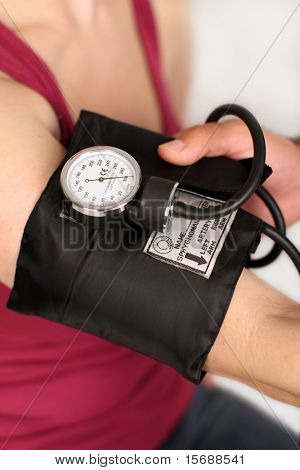 Medical worker checking woman's blood pressure