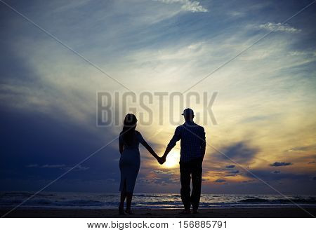 Mid low angle shot of the romantic couple standing on the beach and holding hands together