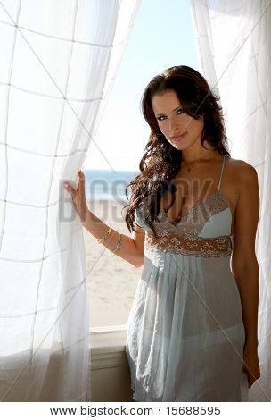Beautiful brunette lingerie model at a beach house window
