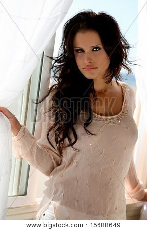 Beautiful brunette model at a beach house window