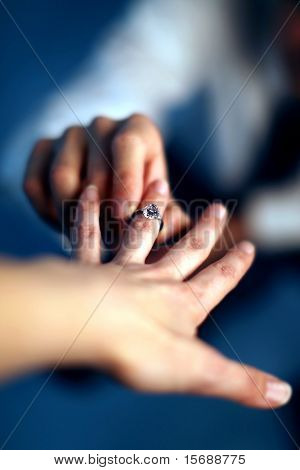 A man proposing and putting a ring on a woman's finger