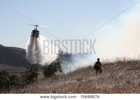 Helikopter druppels water op een borstel vuur als een brandweerman horloges op