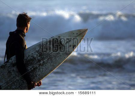 Ein Surfer-Holdng sein Board und Check-out die Wellen