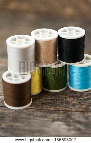 Close up of multi-colored thread bobbins on a wooden table