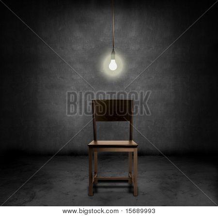 Uma cadeira vazia e bulbo de luz pendurado em um quarto escuro