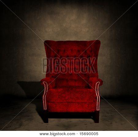 Una silla de terciopelo rojo grungy en un cuarto oscuro