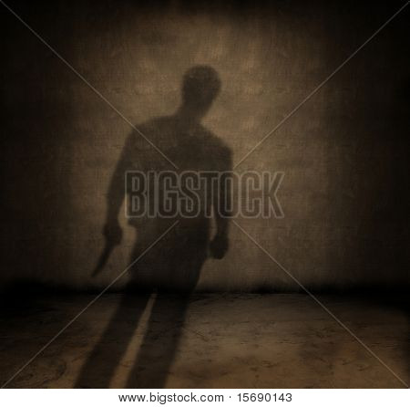 Shadow of a man with a knife in a dark grungy room