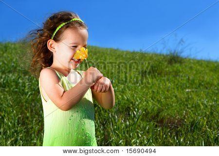 Kleines Mädchen in eine Wiese riecht ein orange Mohn