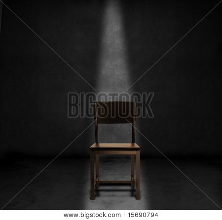 An empty chair and spotlight in a dark room