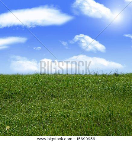 Bright Summer sky and green grassy hill