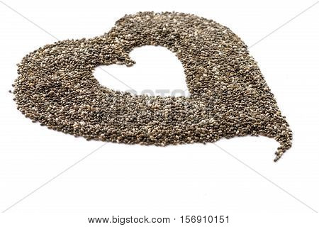 chia seeds shaped into a heart shot from a side view with a selective focus on a white background