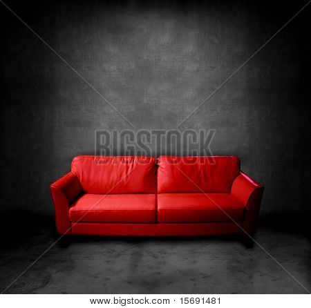 A red leather couch in a dark room