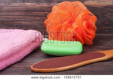 double-sided grater for feet with soap on a wooden background.