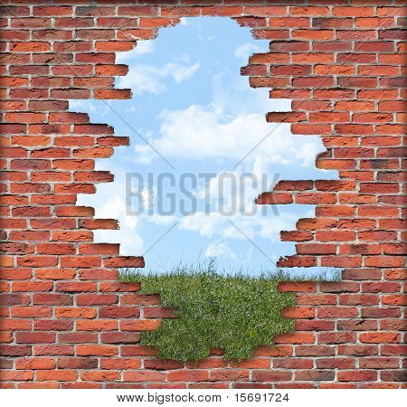 Old crumbling brick wall in front of a grassy hill with a cloudy sky