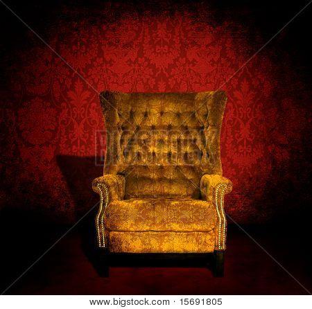 Una silla de terciopelo de oro grungy en un cuarto oscuro con rojo fondos victoriana