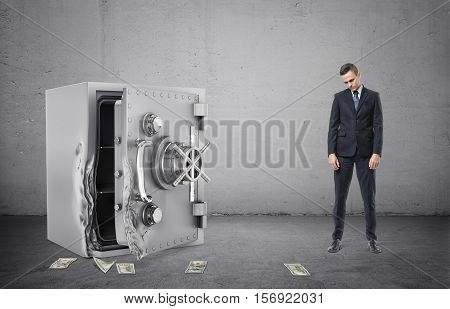 A safe with its door broken open, several banknotes on the ground and the disappointed businessman full height on the grey background. Business and banking. Failures and problems. Theft and property crime.