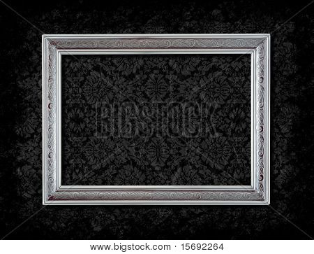 Grungy silver frame on black floral wallpaper