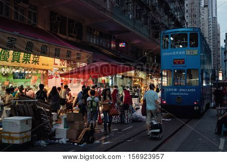 HONG KONG - October 2016: Evening view of wet market with people and double-decker tram.