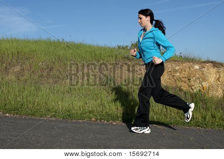 Young athletic woman running on a trail