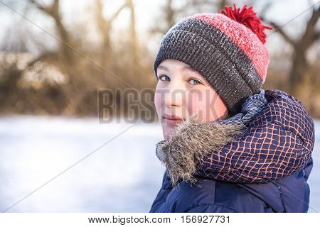 Child turn around and looking at the camera in winter park during winter holidays