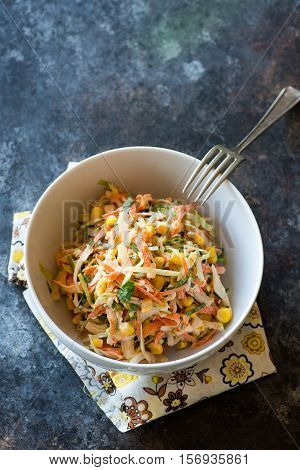Fresh cabbage corn and carrot coleslaw salad in bowl mayonnaise dressing. Dark background top view closeup copy space