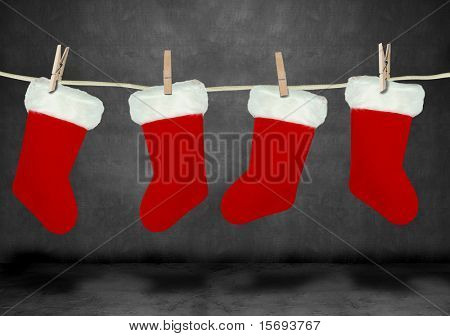 Christmas stockings hanging from a clothes line in a dark room