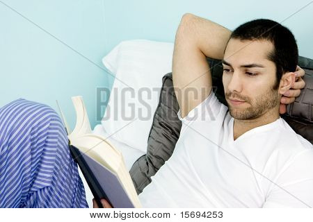 Attractive man lying in bed reading