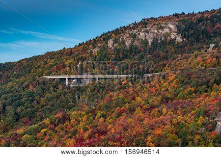 Linn Cove Viaduct In Fall from Rough Ridge against a blue sky