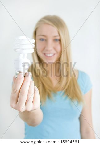 Young woman holding an energy efficient light bulb