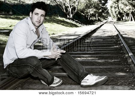 Cross processed man sitting on tracks