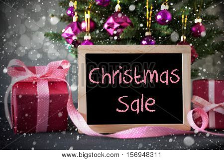 Christmas Tree With Rose Quartz Balls, Snowflakes And Bokeh Effect. Gifts Or Presents In The Front Of Cement Background. Chalkboard With English Text Christmas Sale