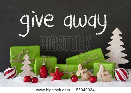 English Text Give Away. Green Gifts Or Presents With Christmas Decoration Like Tree, Moose Or Red Christmas Tree Ball. Black Cement Wall As Background With Snow.
